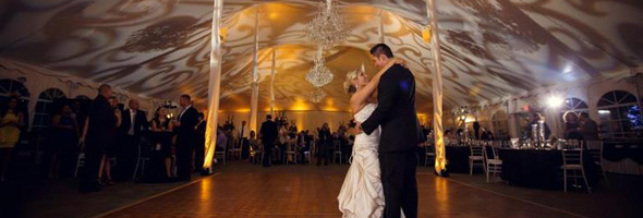 wedding couple dancing with event lighting gobos and amber uplighting in the background tent